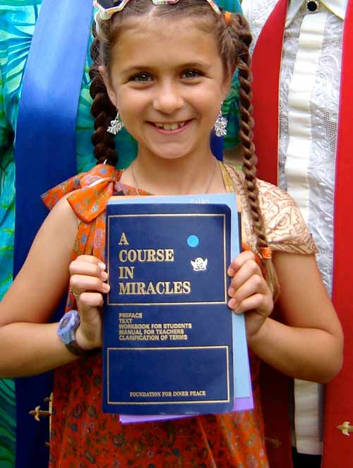 photo: Alzena, standing holding a soft cover copy of A Course In Miracles