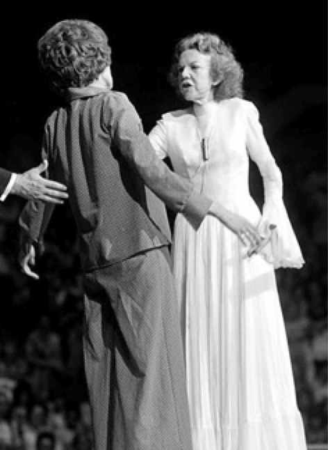 "photo: Evangelist Kathryn Kuhlman ""performing a healing"" on stage"